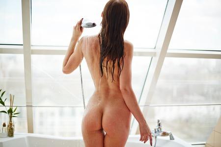 femme se deshabille: Vue arrière de la femme elle-même attrayante éclaboussures de la douche