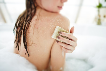 undressed: Young woman exfoliating her skin with soap