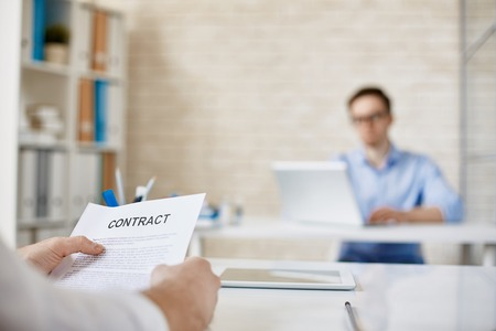 working environment: Hands of male employee with contract over workplace in working environment Stock Photo
