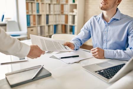 contrato de trabajo: El hombre de negocios dando su colega contrato para leer y firmar