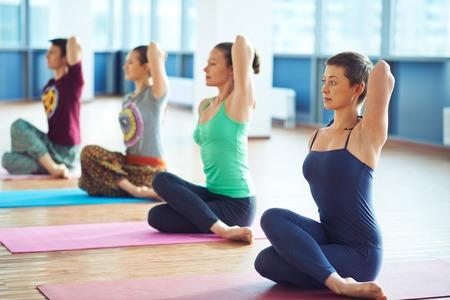 Gruppe von mehreren Menschen, die auf dem Boden Yoga-Übung Standard-Bild - 40023401