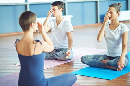 yoga: Girl and guy repeating yoga exercise after their teacher in gym