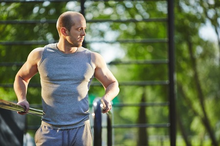 activewear: Sporty man in grey vest training in natural environment