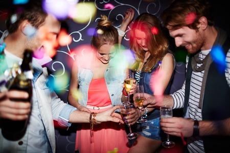 クラブでパーティーを持つシャンパンのフルートを持つ若い友人のグループ