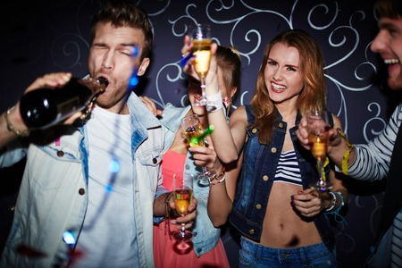 Group of clubbing friends with champagne having fun at party