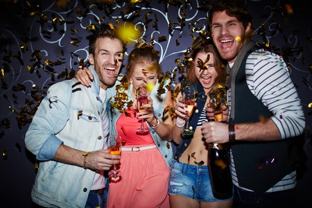 Ecstatic friends with champagne having fun at party Stock Photo