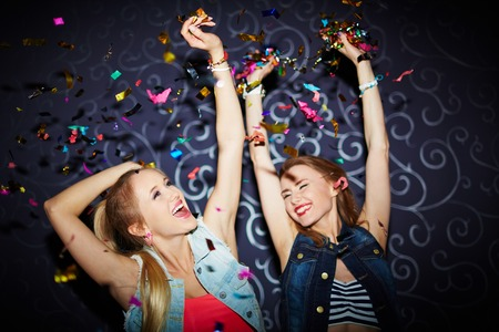 Two energetic girls dancing in night club