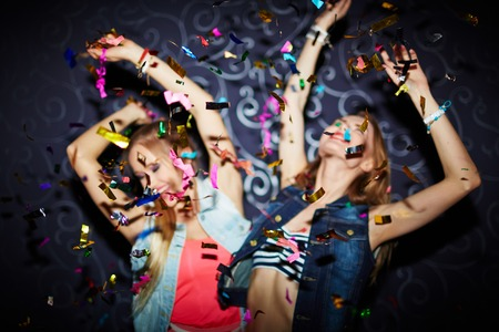 clubber: Two energetic girls dancing in confetti falling