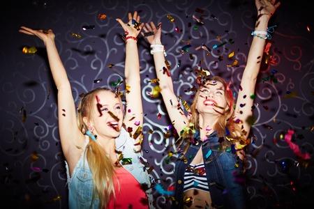 persone che ballano: Due ragazze che ballano energetici con le braccia alzate
