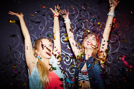 young people fun: Two energetic girls dancing with raised arms