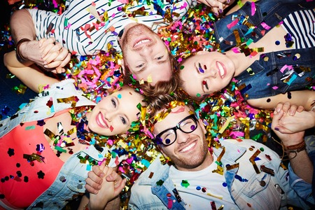 Cheerful friends lying on the floor in nightclub and looking at camera