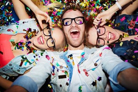 Cheerful friends lying on the floor in nightclub and making selfie