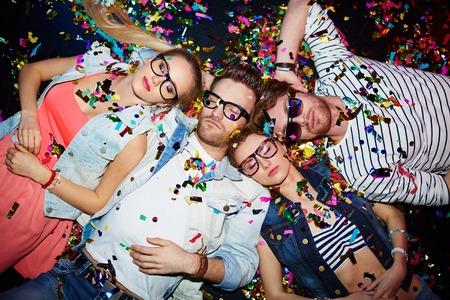 pijamada: Jóvenes amigos que duermen en confeti en el suelo en club nocturno después de la fiesta