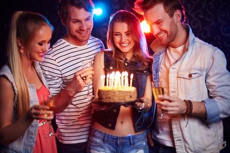 축하: 생일 파티에서 촛불을보고 샴페인과 케이크와 함께 두 젊은 커플