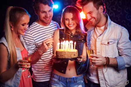 birthday celebration: Two young couples with champagne and cake looking at candles at birthday party