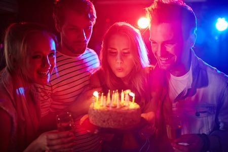 kerze: Junges Mädchen bläst Kerzen auf Geburtstagskuchen zwischen ihren Freunden