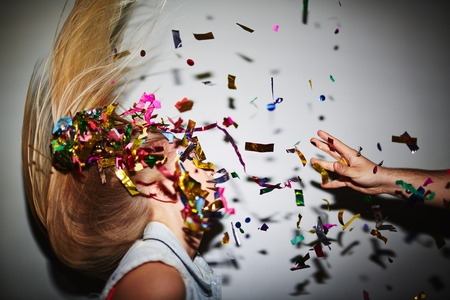 throwing: Blond girl dancing in nightclub while man throwing confetti at her