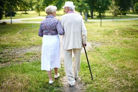 persona caminando: Vista trasera de la tercera edad bien vestidos dando un paseo en verano
