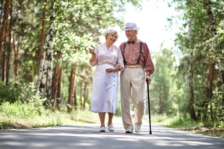 Portrait of happy senior couple walking in park Stock Photo
