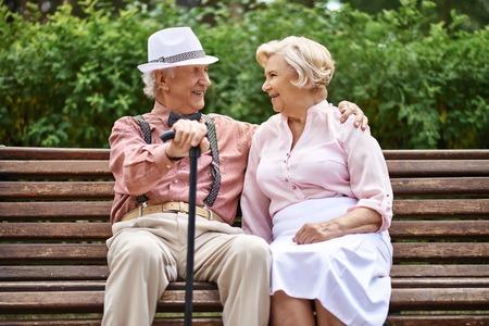 Happy senior paar zitten op een bankje in het park en praten Stockfoto