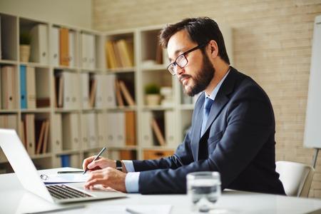 hombres jovenes: Hombre navegaci�n empleado de oficina en la computadora port�til de la informaci�n necesaria