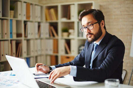 busy beard: Serious businessman browsing in laptop at workplace