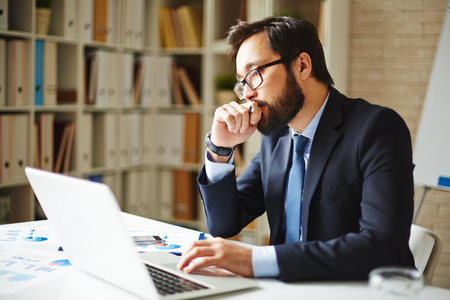 pensive: Pensive businessman sitting in front of laptop in office Stock Photo