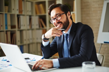 Elegant businessman in eyeglasses networking in office