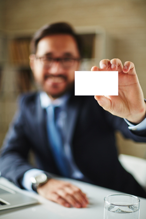 introducing: Hand of businessman with blank card introducing himself to partner