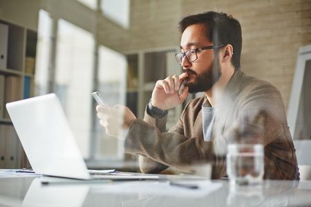 Modern office worker writing sms Standard-Bild