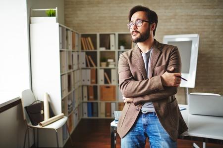 オフィスで短い休憩を持つアジア系のビジネスマン 写真素材