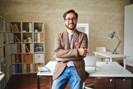 アジア系のビジネスマンがオフィスで彼の机のそばに立って