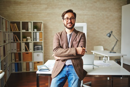 joyful businessman: Asian businessman standing by his desk in office