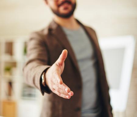 Businessman giving his hand for handshake to partner Foto de archivo