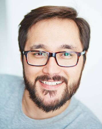 closeup portrait: Happy young man with beard looking at camera Stock Photo