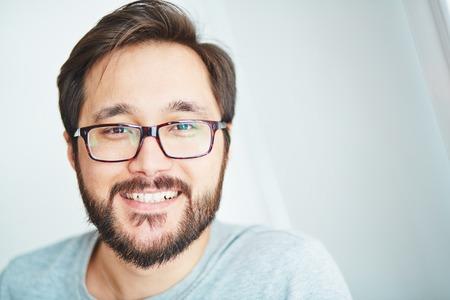こぼれるような笑顔でカメラ目線の眼鏡で幸せな若い男