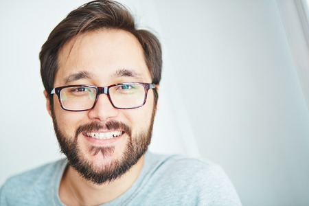 hombre con barba: Hombre joven feliz en gafas mirando a la cámara con sonrisa de pez