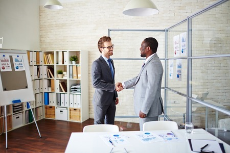 business deal: Confident managers handshaking in office after signing contract Stock Photo