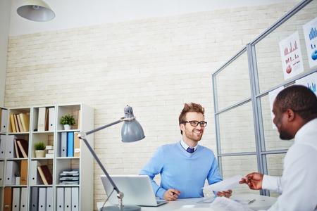 Uomo africano che passa sopra il suo curriculum di datore di lavoro in ufficio