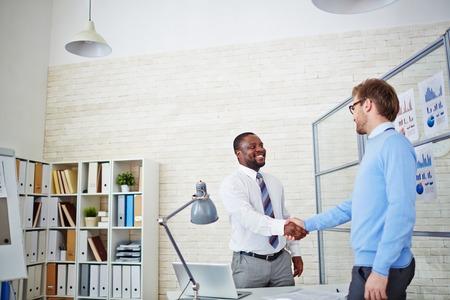felicitaciones: Empresario joven felicitando hombre recién contratado