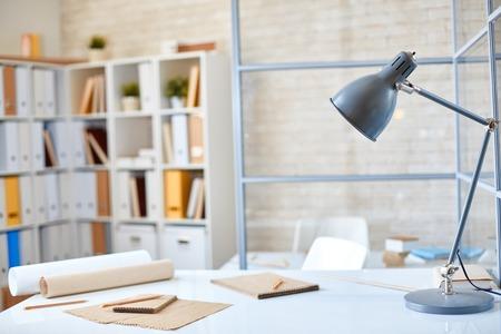 Bureau met lamp, papier en potloden in kantoor