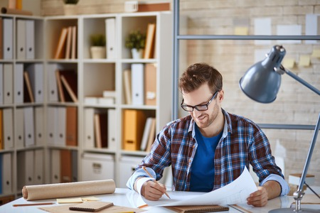 corrections: Young architect making corrections in blueprint Stock Photo