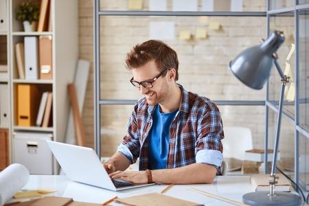 Jonge man browsen in de laptop in het kantoor