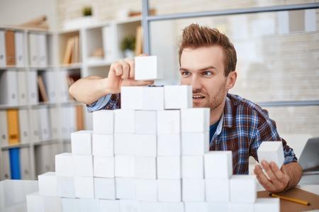 piramide humana: Hombre de negocios creativo en ropa casual papel pirámide edificio