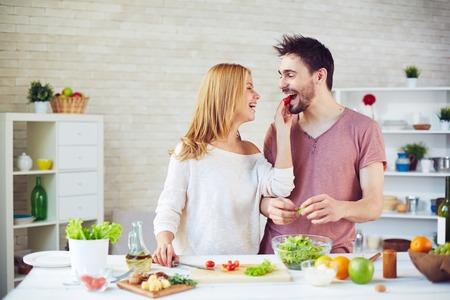 サラダを調理しながら夫にトマトを与える幸せな女性