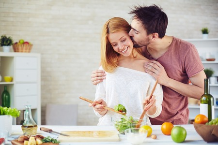 Young man kissing his wife while she mixing up salad ingredients
