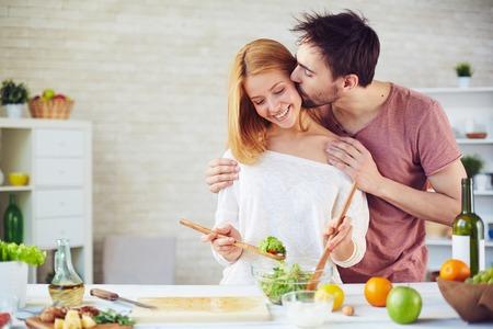 parejas romanticas: Hombre joven que besa a su esposa mientras ella mezclando ingredientes de la ensalada Foto de archivo