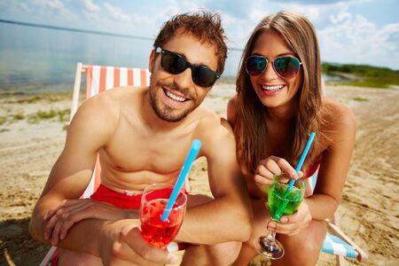 mujeres felices: Feliz pareja con c�cteles que tiene partido en la orilla del mar