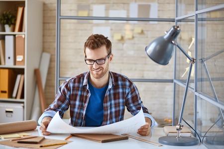 ejecutivo en oficina: Arquitecto joven que mira el modelo en el cargo Foto de archivo