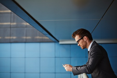 serious businessman: Businessman with cellphone reading or writing sms